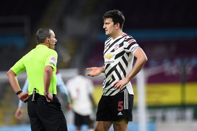 Harry Maguire (right) talks to referee Kevin Friend